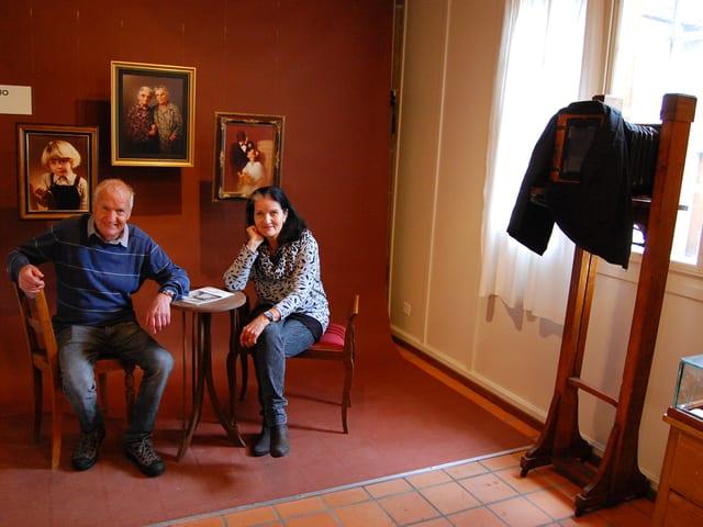 Mann und Frau sitzen in einer Foto-Ausstellung.