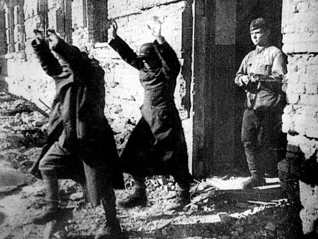 Zwei deutsche Soldaten gehen mit erhobenen Händen einem sowjetischen Soldaten voran.
