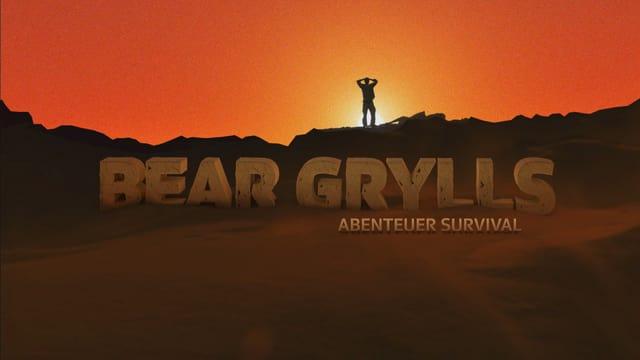 Bear Grylls steht am Abgrund und blickt in einen feuerroten Himmel hinaus. Darunter ist gross der Schriftzug Bear Grylls - Abenteuer Survival im Sand zu sehen.
