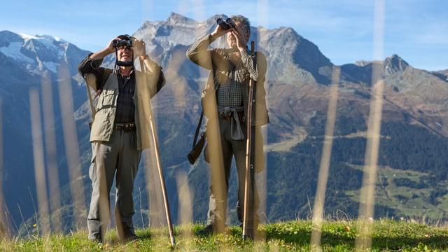 Zwei Jäger mit Ferngläsern in den Bündner Bergen.