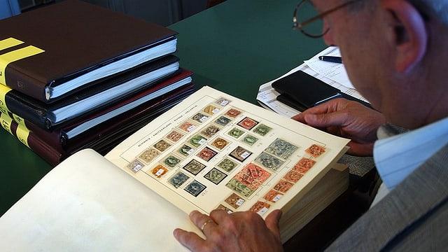 Mann schaut sich ein Buch mit Briefmarken an.