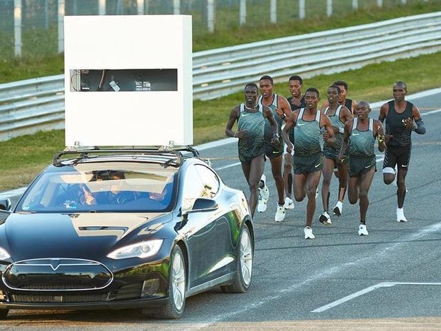 Drei Marathonläufer hinter einem Elektro-Auto und zahlreichen Tempomachern.