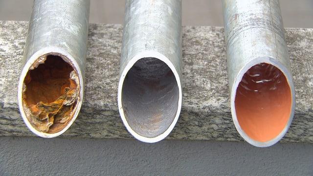 Drei Rohre in verschiedenen Stadien: korrodiert, gesäubert und mit Epoxidharz ausgekleidet.
