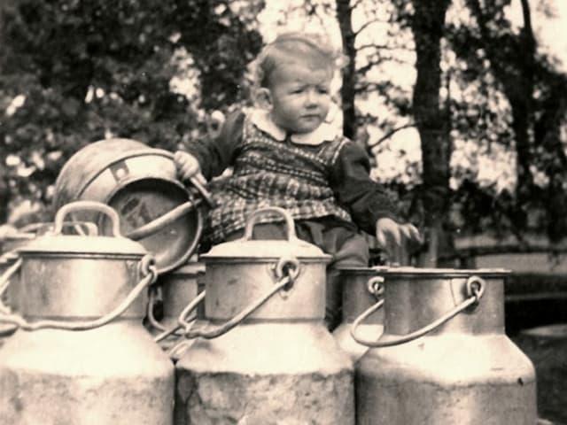 Ein Kind sitzt auf Milchkannen.