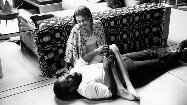 Szene aus einem Film: Ein Mann in Hemd und Anzughose liegt am Boden. Eine junge Frau in weissem Shirt sitzt neben ihm an eine Couch gelehnt, die Beine hat sie über den Mann gelegt. Die beiden lächeln sich an.