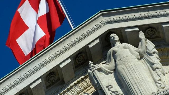 Das Dach des Bundesgerichts mit Schweizerfahne und Justizia.