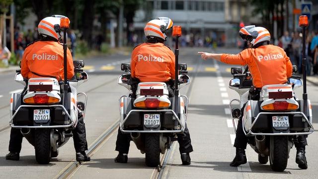 Drei Polizeimotorräder mit Fahrern von hinten auf einer Strasse