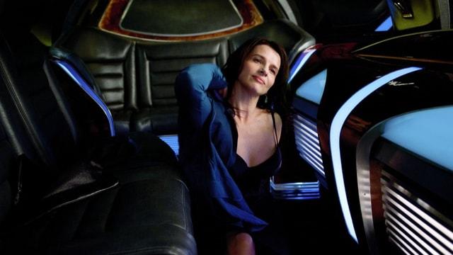 Eine Frau räkelt sich in einer Limousine.