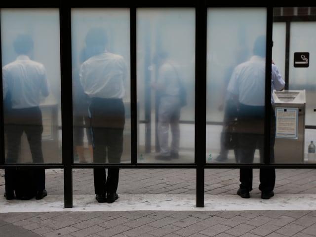 Männer stehen in einem abgeschlossenen Raucherabteil.