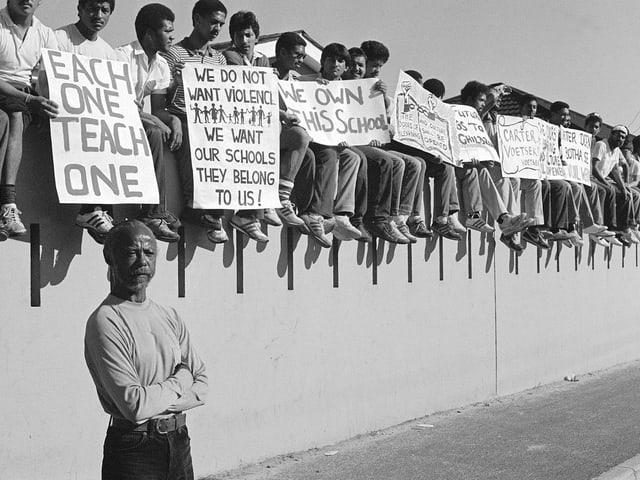 James Matthews protestiert zusammen mit Schülern. Sie sitzen alle auf einer Mauer und halten Plakate.