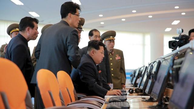 Nordkoreas Machthaber Kim Jong-un sitzt an einem Computer, hinter ihm stehen Beamte und Militärs im sogenannten Sci-Tech Complex in Pjöngjang.