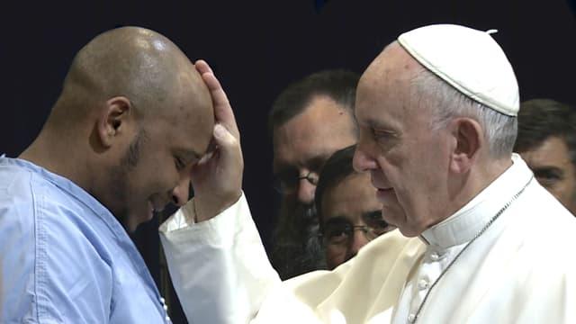 Der Papst segnet einen Mann.