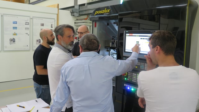 Kunden diskutieren vor einer Maschine der Firma Posalux.