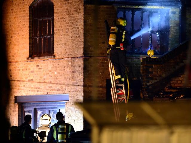 Feuerwehrmann auf Leiter an einem Backsteingebäude mit Fenstern