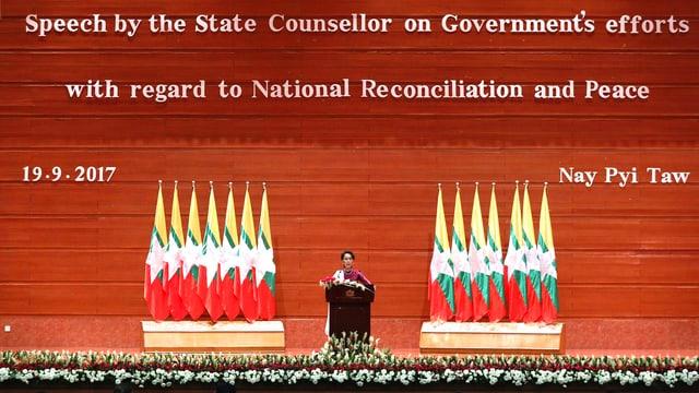 Aung San Suu Kyi steht auf einer immensen Bühne und ist kaum zu sehen.