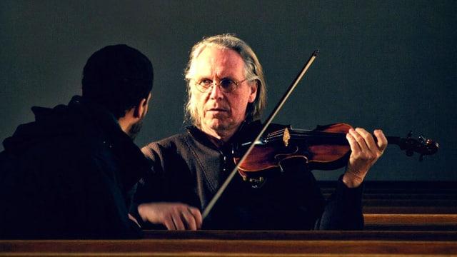 Der Vater mit Violine in der Hand, daneben sitzt sein Sohn.