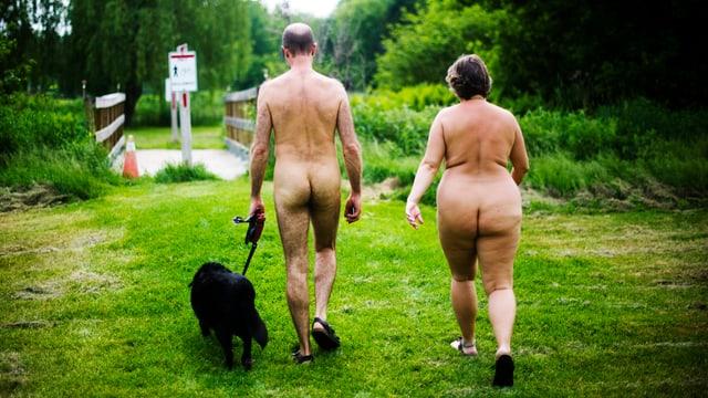 Mann und Frau nackt laufen mit Hund auf grüner Wiese, der Rücken zur Kamera.