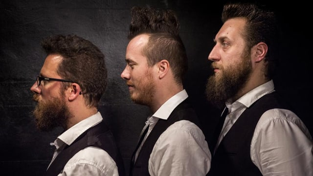 Drei Männer im Profil schauen zu einer Seite.