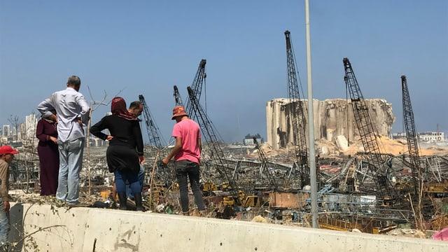 Menschen schauen auf ein Trümmerfeld