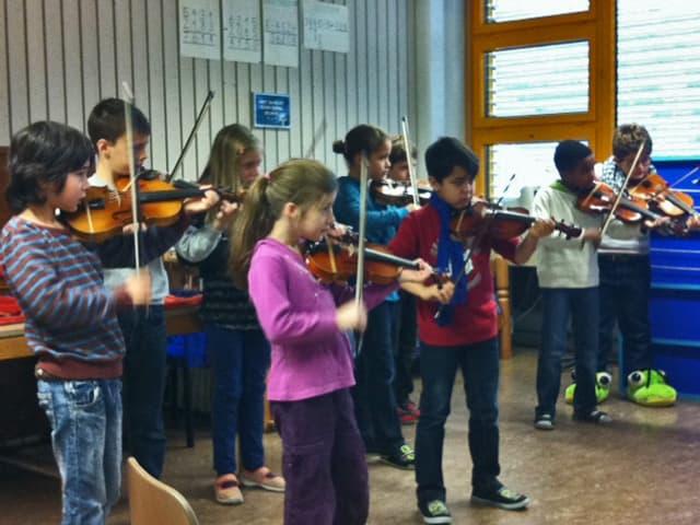 Eine Gruppe von Schulkindern spielt Geige.