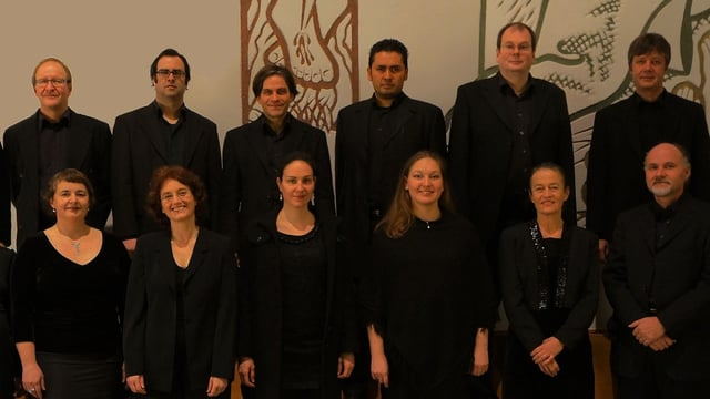 Menschen in schwarzer Kleidung stehen in 2 Reihen