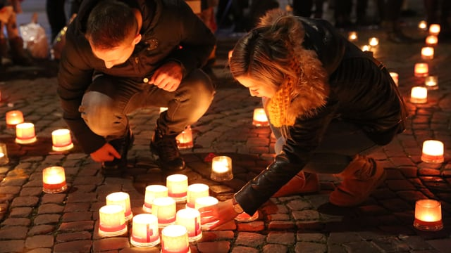 Menschen zünden Kerzen an.