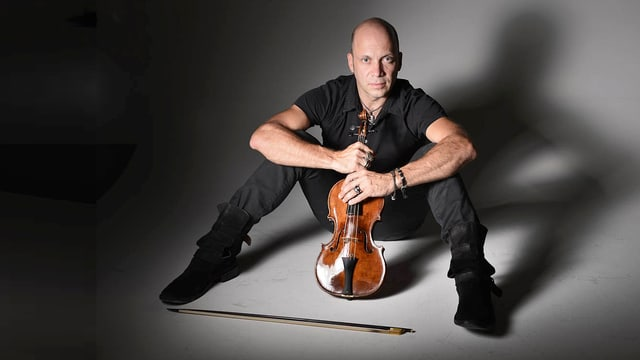 Der schwarz gekleidete Stefano Montanari sitzt am Boden mit gespreizten Beinen, in den Händen hält er eine Geige.