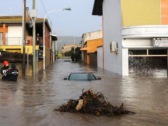 Eine Strasse steht unter Wasser. Man sieht ein untergegangenes Auto.