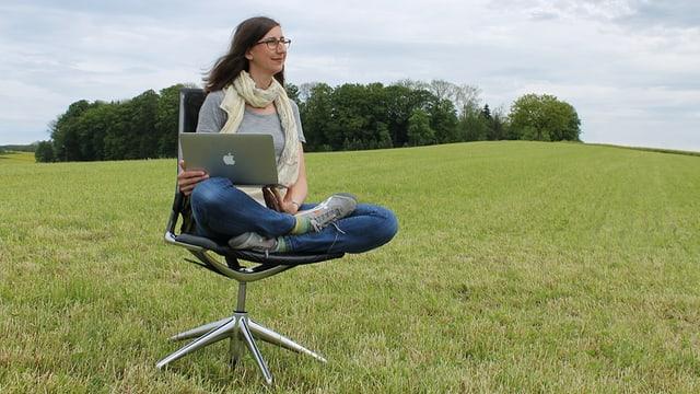Patricia Felber sitzt auf einem Bürostuhl auf einer Wiese und hat einen Laptop auf den Knien.