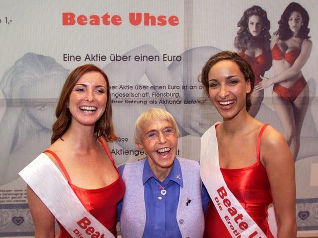 Beate Uhse mit zwei weiblichen Models an ihrer Seiten