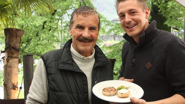 Ivo Adam und Franchino Ferrini mit einer Tessiner Luganighetti-Wurst auf dem Teller.