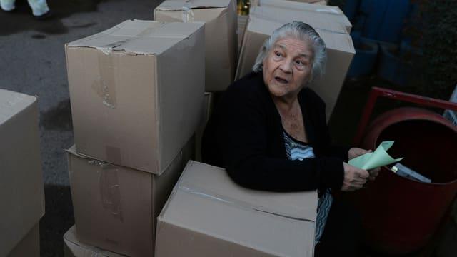 Eine Frau in Santiago sitzt zwischen Lebensmittelpaketen der Regierung.