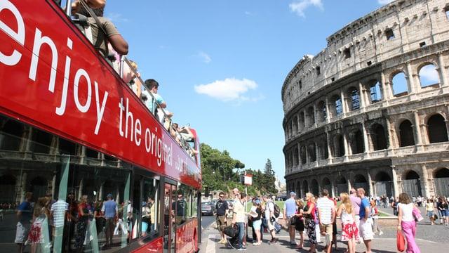 Touristen fahren mit einem Doppeldeckerbus am Kolosseum in Rom vorbei
