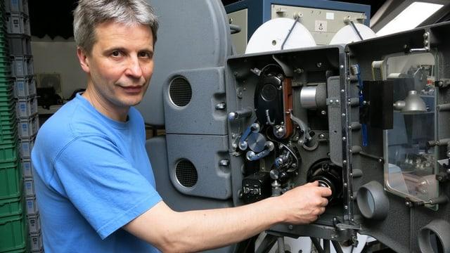 David Landolf dreht an einem alten Projektor.