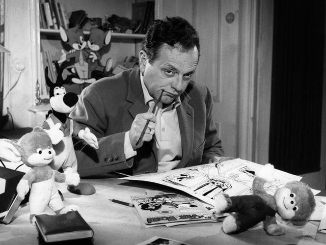 Ein Mann mit Stift im Mund und Comics auf dem Schreibtisch.