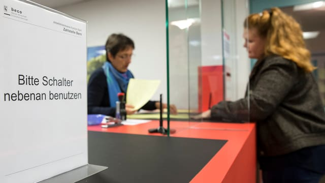 Eine junge Frau steht an einem Schalter, gegenüber eine Beamtin mit einem Blatt in der Hand. Schild: Bitte Schalter nebenan benutzen.
