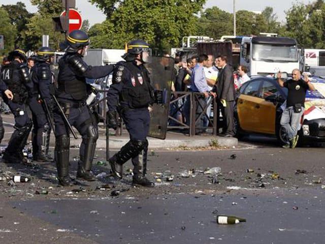 Polizisten in Kampfmontur schreiten zu Autokollone.