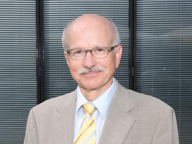 Portrait von Urs Hintermann. Er lächelt in die Kamera.