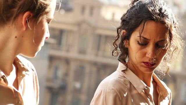 Eine Frau blickt auf eine andere Frau, die wiederum auf den Boden blickt.