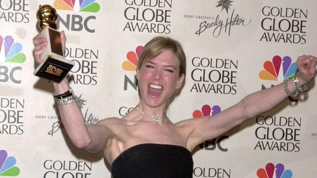 Eine Frau streckt lachend beide Arme in die Höhe. In der rechten hält sie eine goldene Trophäe.