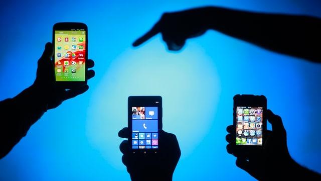 Drei Hände halten vor einer blauen Wand je ein Smartphone in die Luft, eine vierte Hand zeigt mit dem Zeigfinger auf das eine Gerät.