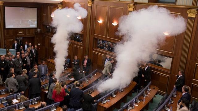 Zwei Tränengaswolken strömen in Sitzreihen des Parlamentes aus.