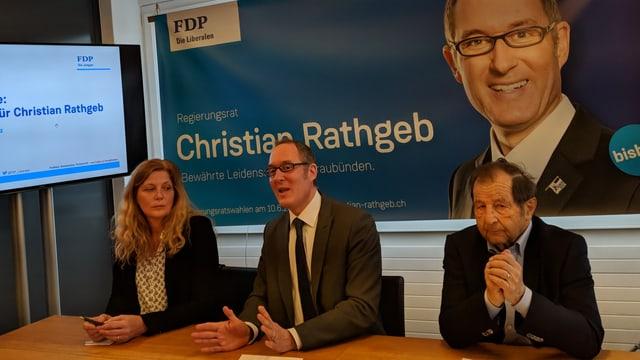 Anna-Margreth Holzinger, presidenta da la cumissiun electorala, Christian Rathgeb, candidat e Silvio Zuccolini, responsabel per las medias.