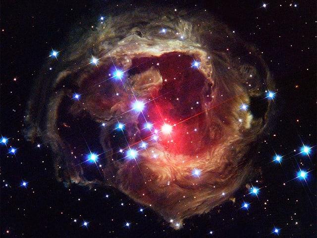 Eine Aufnahme des Hubble Teleskops. Es zeigt einen rötlichen Farbschleier aus abertausenden Punkten. Dazwischen scheinen Sterne, also kleine Sonnen ins Weltall.