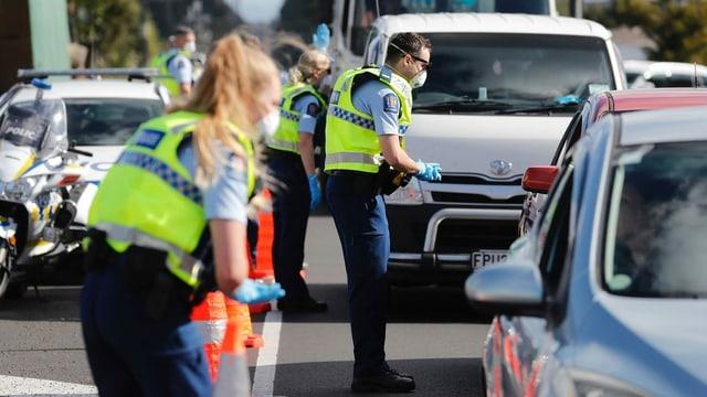 Polizistinnen und Polizisten kontrollieren Autofahrer in Auckland