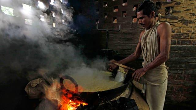Ein Mann bereitet in dichtem Rauch Lebensmittel in einem Imbiss in Kalkutta vor.