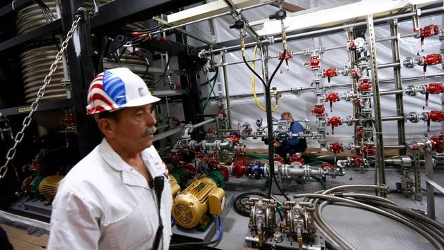 Ein Mann in weissem Overall und Helm vor einer Industrieanlage.