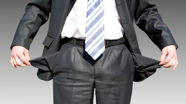 Ein Anzugträger zeigt seinbe leeren Taschen