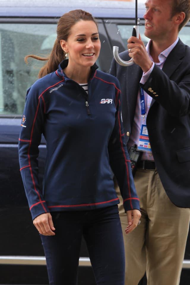 Herzogin Kate lächelt in blauer Fleece-Jacke, während ein Bediensteter für sie den Schirm hält.