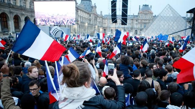Macron-Anhänger mit Fahnen vor dem Louvre.